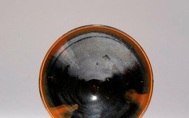 A CHINESE HENAN-TYPE BOWL YUAN/MING DYNASTY The conical body rising to an upright rim, decorated in a black glaze with brown splashes, the lower section of the exterior and the short flared foot left unglazed, 17.8cm. Provenance: from a deceased...