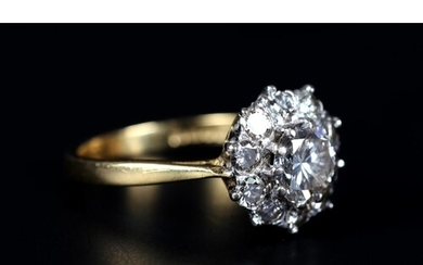 A DIAMOND CLUSTER RING in 18ct yellow and white gold, claw s...