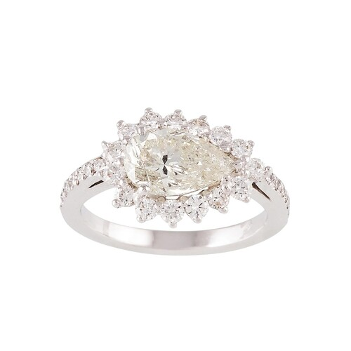 A DIAMOND CLUSTER RING, the pear shaped diamond to a brillia...