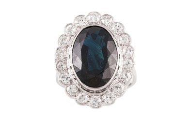 A SAPPHIRE AND DIAMOND OVAL CLUSTER RING, with one oval cut ...