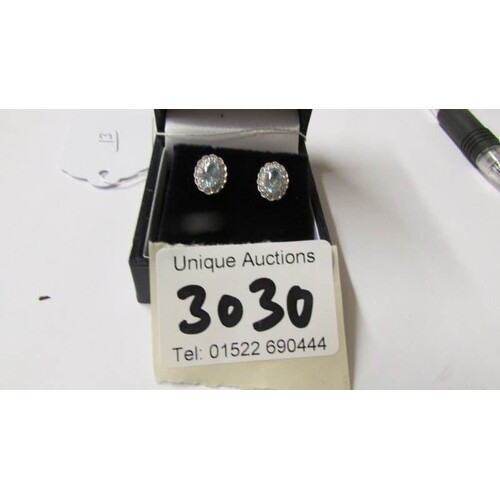 A pair of 18ct white gold aquamarine and diamond earrings of...