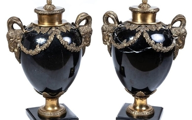 A pair of bronze-mounted black marble urns in...