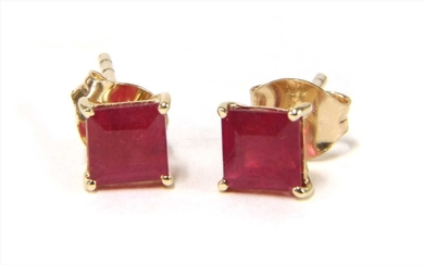 A pair of gold single stone treated ruby stud earrings