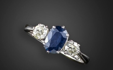A sapphire and diamond three-stone ring, the oval-shaped sapphire set with an old circular-cut diamond to each shoulder in white gold, size O 1/2