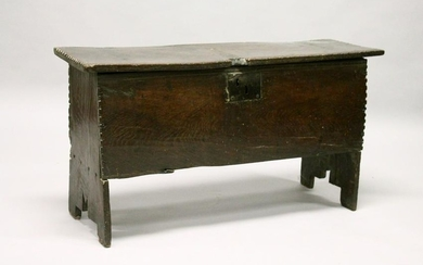 AN 18TH CENTURY OAK SIX PLANK COFFER, with chip carved