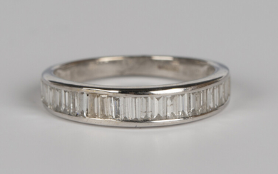 An 18ct white gold and diamond half eternity ring, set with baguette cut diamonds, detailed '75