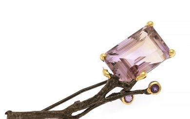 An amethyst brooch set with an emerald-cut and two circular-cut amehysts, mounted in black rhodium plated and partly gilded sterling silver.