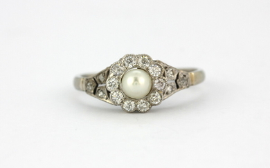 An early 20th century white metal (tested high carat gold) pearl and diamond set ring, (N.5).
