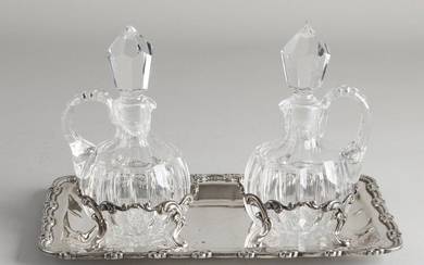 Crystal carafes set on silver tablet, 925/000, Two convex cut carafes with stopper placed on a rectangular tablet decorated with a border with French lilies and palmettes and two holders of curls on 4 legs for the carafes. Composed. 23x14x16cm. In...