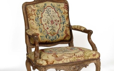 Sculpted beech armchair with a flat shouldered back, decorated with asymmetrical leaf cartouches, rockeries, upholstered with a floral tapestry. Louis XV style Height 102 cm, width 73 cm, depth 60 cm.
