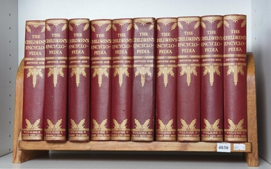 TEN VOLUMES OF THE CHILDREN'S ENCYCLOPEDIA IN A HARDWOOD BOOK STAND