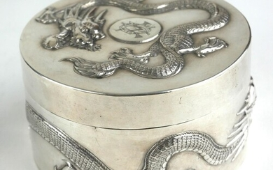 A CHINESE SILVER CIRCULAR BOX AND COVER Decorated in relief ...
