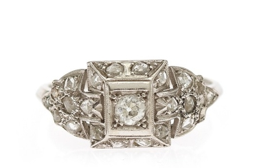 A diamond ring set with one old-cut diamond encircled by numerous rose-cut diamonds, mounted in platinum. Size 58.