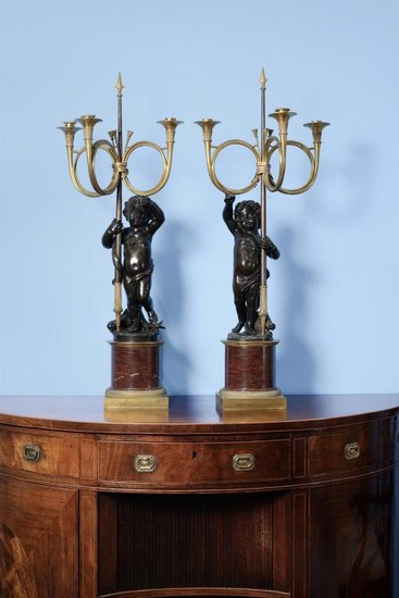 A pair of French gilt and patinated bronze, and rouge griotte mounted figural three light candelabra