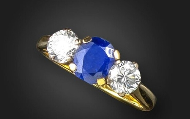 A sapphire and diamond three-stone ring, the oval-shaped sapphire is flanked with round brilliant-cut diamonds in yellow gold, London hallmarks for 18ct, 1973, size M