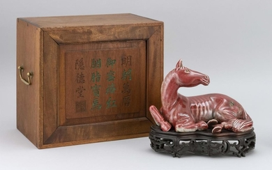 """CHINESE PEACHBLOOM GLAZE PORCELAIN FIGURE OF A RECLINING HORSE Length 9"""". With wooden stand and fitted carrying case with calligraph..."""