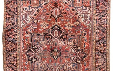"""ORIENTAL RUG: HERIZ 8'2"""" x 11'3"""" Central red, ivory and navy blue gabled medallion on a rust red field above an ivory subfield with.."""