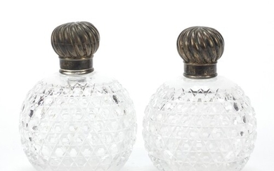 Pair of Victorian cut glass scent bottles with silver lids b...