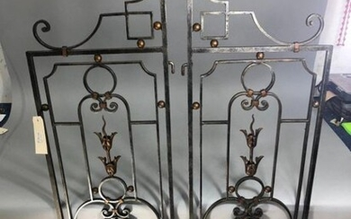 Pair of wrought iron apartment grills opening to two leaves decorated with floral bundles and leaves in gilded cut sheet metal. 20th century.