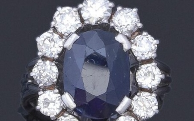 """Ring """" Fleur """" in white gold and platinum, set with an oval faceted sapphire in a ring of brilliant-cut diamonds. Total weight of diamants : approx. 4.7 carats. Turn of doigt : 53 (with cutting ring). P. Brut : 8.9 g."""