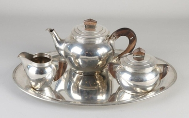 Silver tea service on tray, 835/000, Art Deco. Tea pot, milk jug and sugar bowl with a sphere model with wooden handles and a triple fillet rim. The service is placed on an oval silver tray. The entire service is equipped with a hammer-blow treatment...