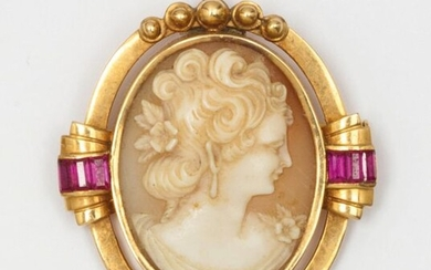 Yellow gold brooch, adorned with a shell cameo representing the profile of a woman with calibrated red stones. Dimensions: 3.5 x 3.8cm. Raw weight: 12.4g.