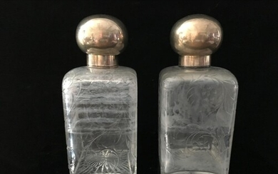 A pair of cut glass and French white metal perfume flasks, o...