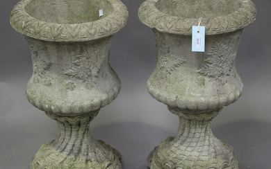 A pair of late 20th century cast composition stone garden urns, the waisted bodies raised on shell d