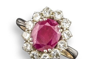 A ruby and diamond cluster ring, the oval-shaped...