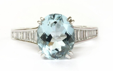 A white gold aquamarine and diamond ring, an oval mixed cut aquamarine, claw set to tapered shoulders, channel set with a graduated row of baguette cut diamonds, with flat section shank. Tested as approximately 18ct gold. 5.70g. Finger size O