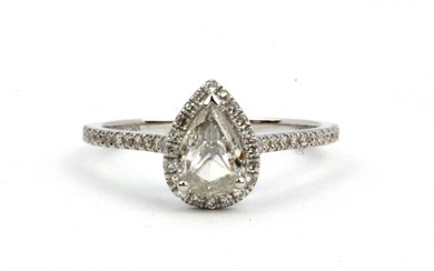 An 18ct white gold solitaire ring set with a pear cut diamond surrounded by brilliant cut diamonds, approx. 0.7ct pear centre, colour H, cla