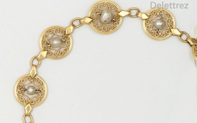 Articulated yellow gold bracelet with round filigree links, each set with a cultured pearl. Length: 19.5cm. Gross weight: 14.2g.