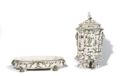 Moustiers Covered wall lamp fountain and its earthenware basin decorated in green monochrome with grotesque figures on terraces, the oval basin resting on four lion-shaped feet, the side holds in the shape of a satyr mask. 18th century. H. 53 cm, L...
