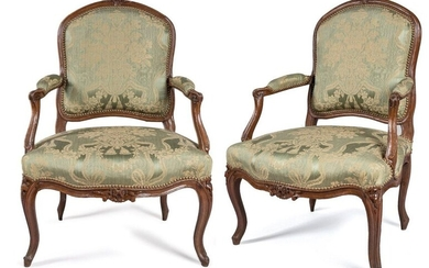 TWO QUEEN LOUIS XV FALLS in moulded and sculpted beech wood, the violin-shaped backrests, decorated with the cushioning of flowers surrounded by a garland of plants or a bouquet, the armrests with cuffs ending in windings, the consoles slightly moved...