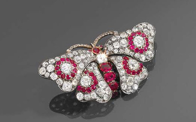9K (375) gold and silver butterfly-shaped brooch with outstretched wings paved with old-cut diamonds and rubies, the body formed of oval rubies of increasing size and a larger diamond.
