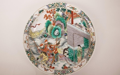 A Chinese famille verte porcelain charger decorated with war...
