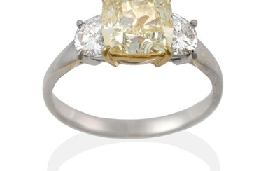 A Diamond Three Stone Ring, the central fancy light yellow...