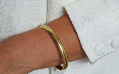 A gold bangle. the opening gold blangle is made of...