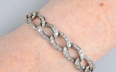 A pave-set diamond curb-link bracelet.