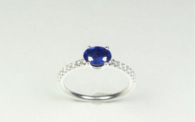 Ring in 18K (750/oo) white gold centered on an oval sapphire calibrating approximately 0.90 ct. and supported by two lines of brilliant-cut diamonds. TDD 52.5. Gross weight: 2.7 g.