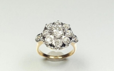 Ring in 18K (750/oo) yellow gold and platinum (850/oo) with a daisy pattern centered on an old cut diamond calibrating approximately 0.95 ct in a surround and a shoulder of old cut diamonds calibrating approximately 1.40 ct together. TDD 53. Gross...