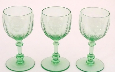 Three green glass pedestal wine glasses with engraved