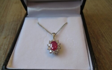 18ct White gold oval ruby and diamond cluster pendant, the r...