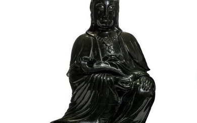 A Chinese serpentine figure of seated Guanyin