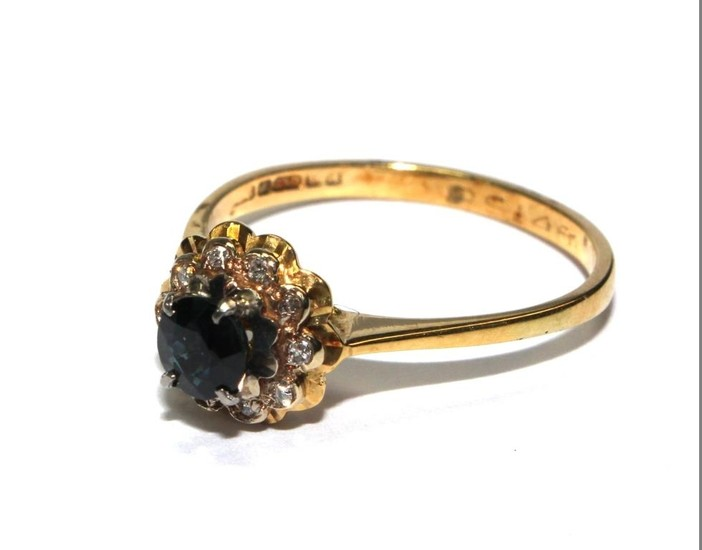 An 18 carat yellow gold ring set with diamonds and sapphires