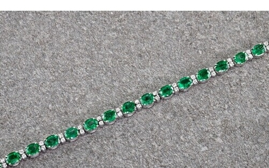 An 18ct white gold, emerald and diamond bracelet, the oval c...