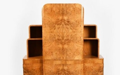 An Art Deco burr walnut veneer cocktail cabinet probably Epstein, L'Odeon form, two central twin door fitted cabinets, the top compartment with electric light, flanked with smaller side cabinets below stepped shelves, fitted with suite of glasses...
