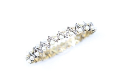 Articulated bracelet in 18k (750) yellow gold and silver holding a double line of small probably fine pearls alternating with geometric lines of small rose-cut diamonds.