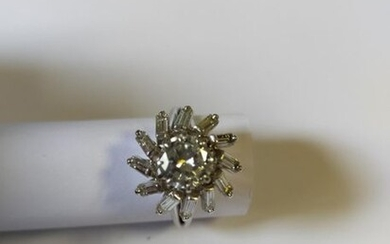 Ring in 18K (750 thousandths) white gold stylizing a flower centered on a brilliant-cut diamond of about 1.30 ct in a star-shaped setting set with baguette-cut diamonds. PB: 5.43 g. Resoldering ring.