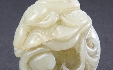 A CHINESE CELADON JADE CARVING, the pebble carved with